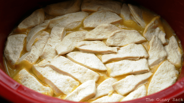 sliced biscuit dough on chicken and sauce in crockpot