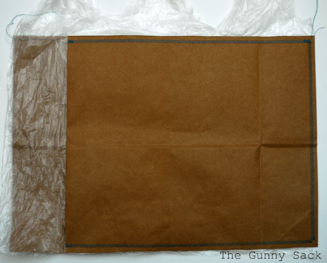 brown bag envelope with blue stitching lined with plastic