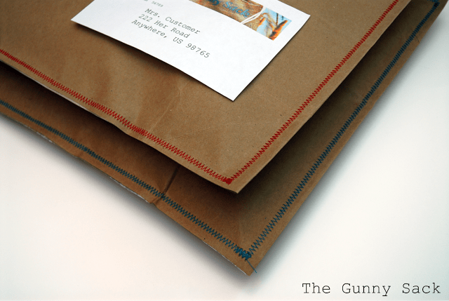 two brown bag envelopes with colorful stitching