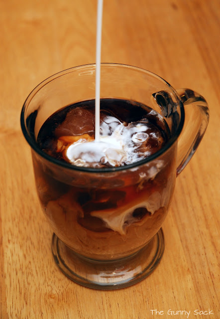 pouring coffee cream into iced coffee
