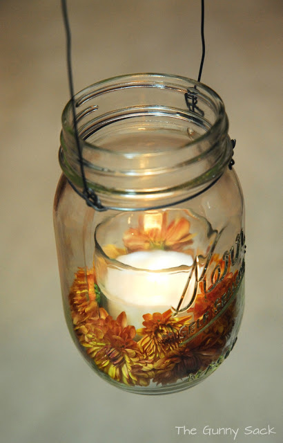 mason jar with lit candle and mums