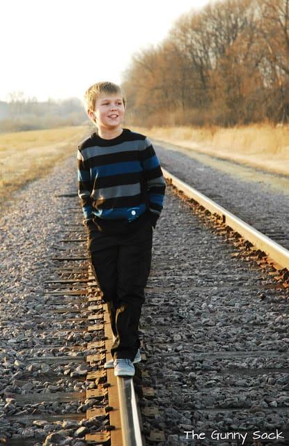 boy on railroad tracks