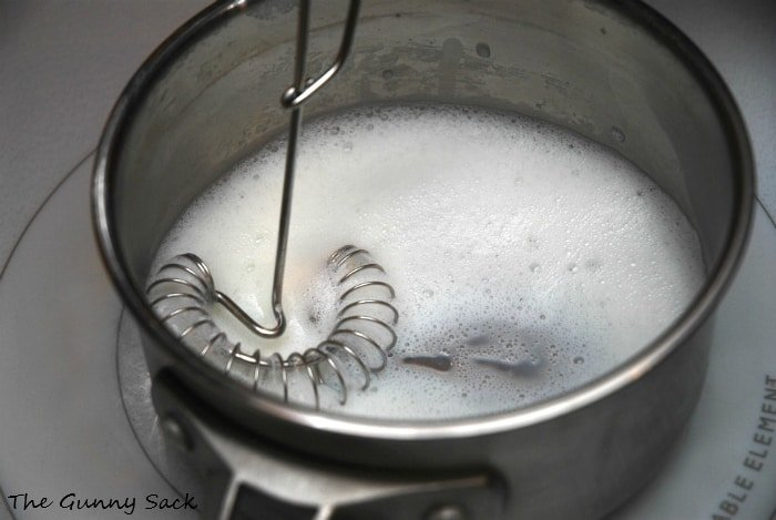 whisking milk in pot