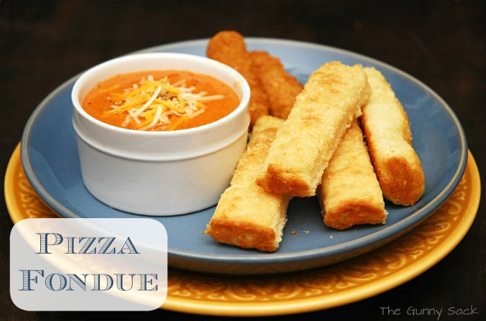 pizza fondue and breadsticks on plate