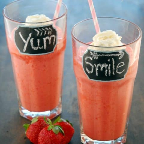 strawberry smoothies in glasses with whipped cream and straws
