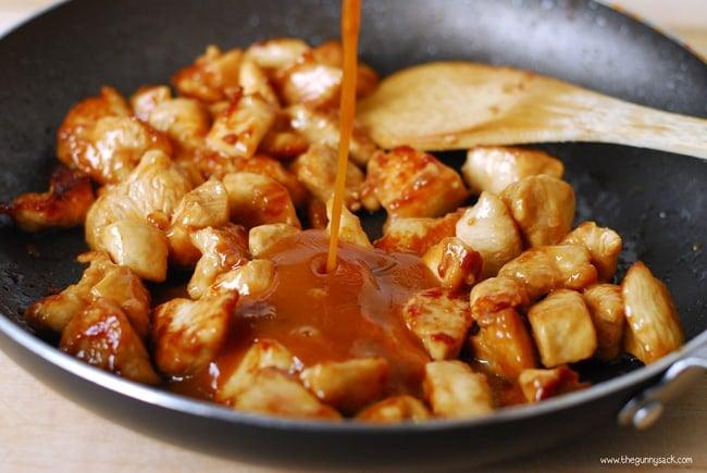 Orange chicken sauce pouring into skillet