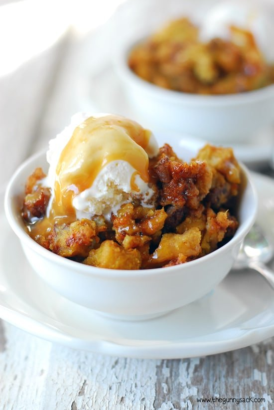 dish of slow cooker pumpkin pecan bread pudding with vanilla ice cream and caramel sauce on top