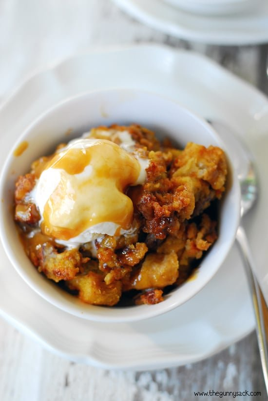 serving of slow cooker pumpkin pecan bread pudding topped with vanilla ice cream and caramel