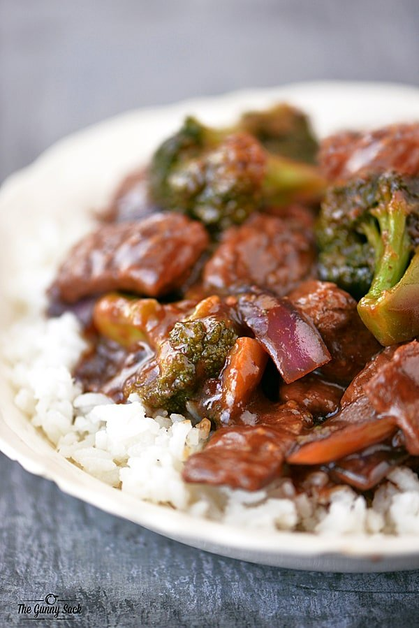 Beef and Broccoli over rice in a white bowl
