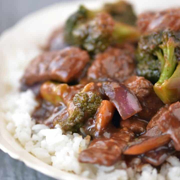Beef and Broccoli on rice in a white bowl