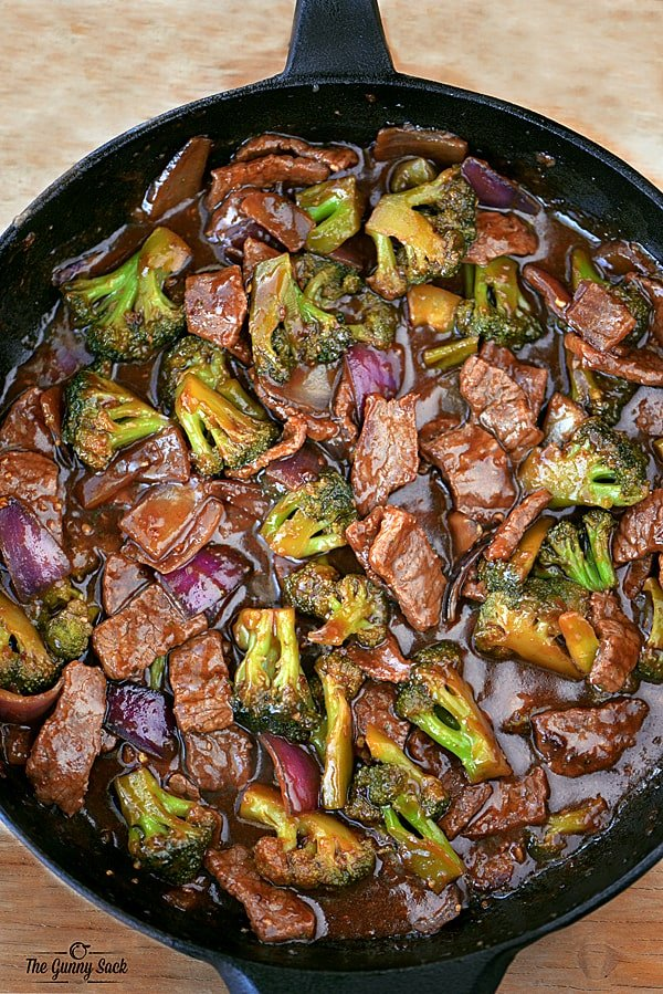 beef and broccoli with onions in a cast iron skillet