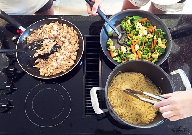 three pans on a stovetop making stir fry