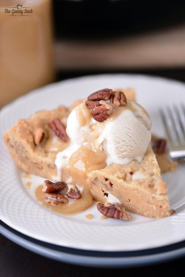Maple Cream Caramel Sauce on top of a Maple Pecan Caramel Skillet Cookie with vanilla ice cream