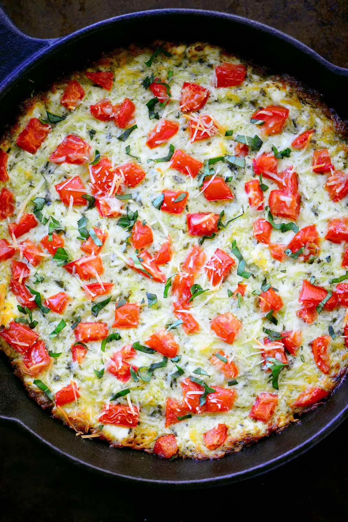 golden brown cheese with tomatoes in a skillet