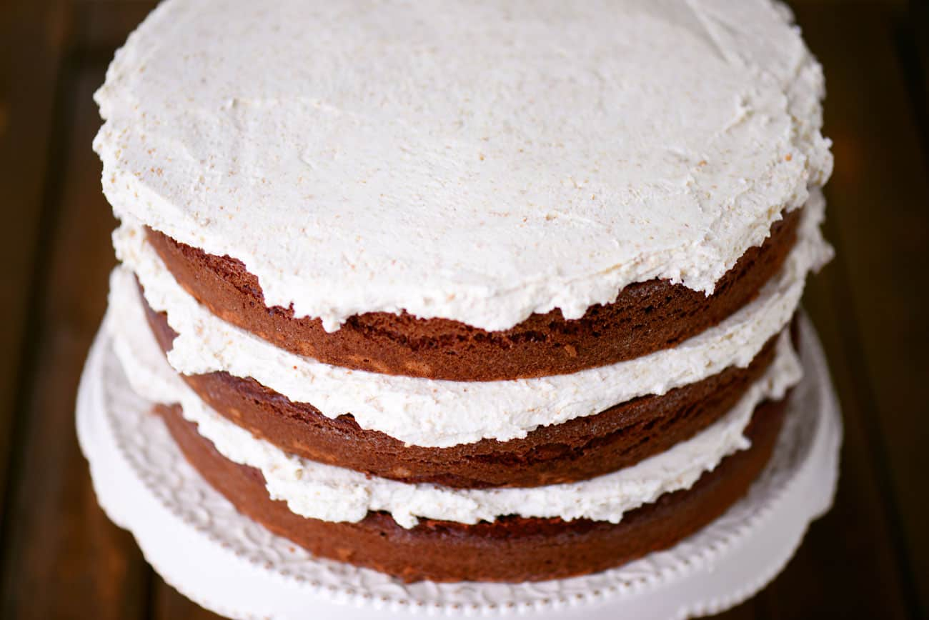 three chocolate cakes stacked with buttercream frosting between each layer