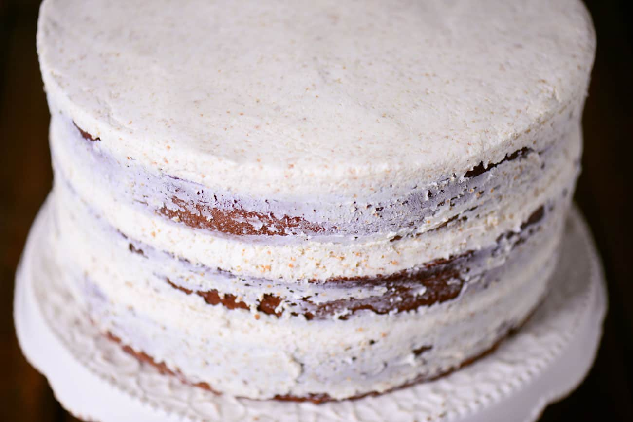 three cakes stacked and lightly frosted with white buttercream frosting