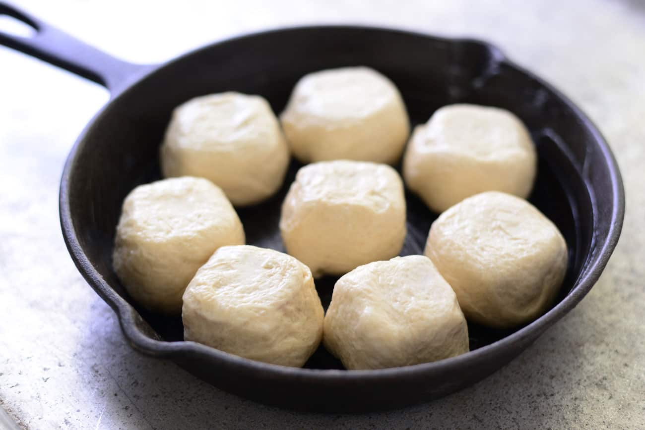 balls of dough in a cast iron skillet