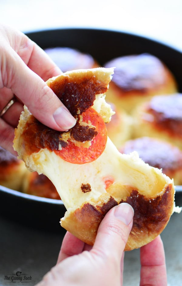 two hands pulling apart a pepperoni pretzel ball with melted cheese inbetween
