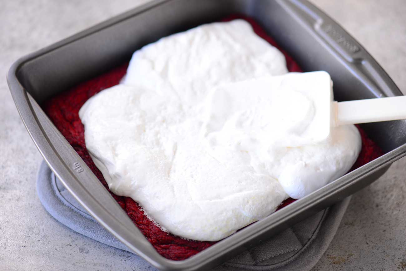 spreading marshmallow cream over red velvet cake layer