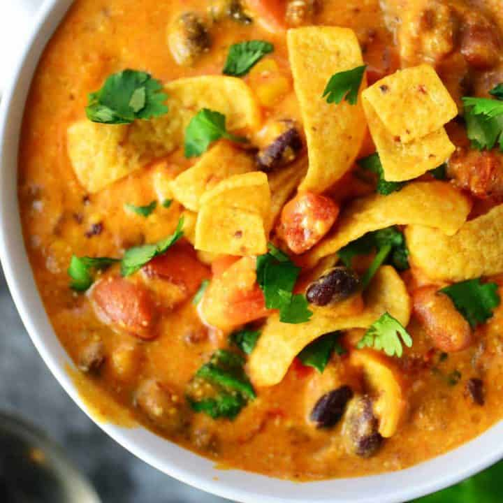 slow cooker taco soup in a white bowl with corn chips and cilantro