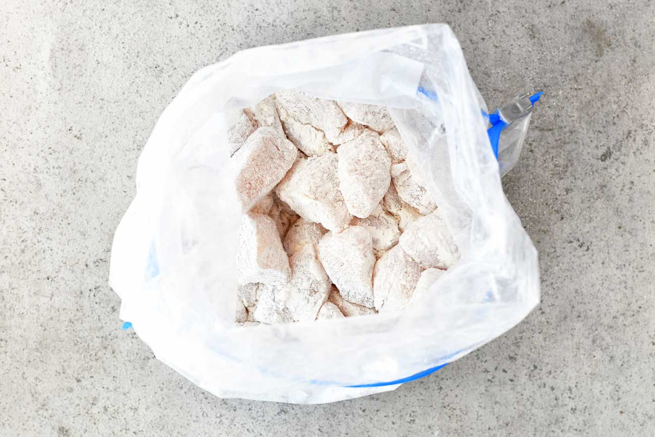 honey garlic chicken pieces coated with flour in a plastic bag