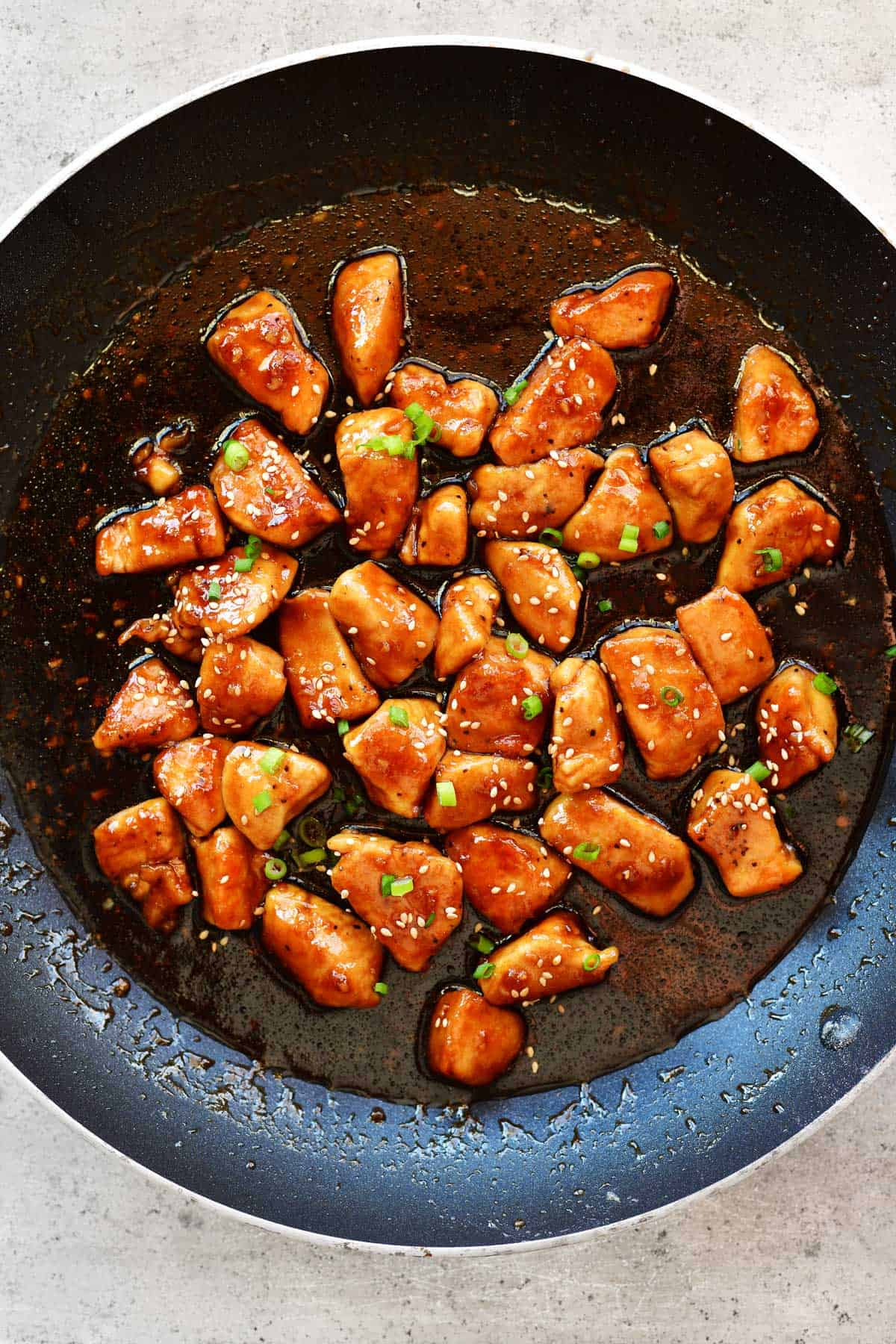honey garlic chicken in a saucepan with sesame seeds