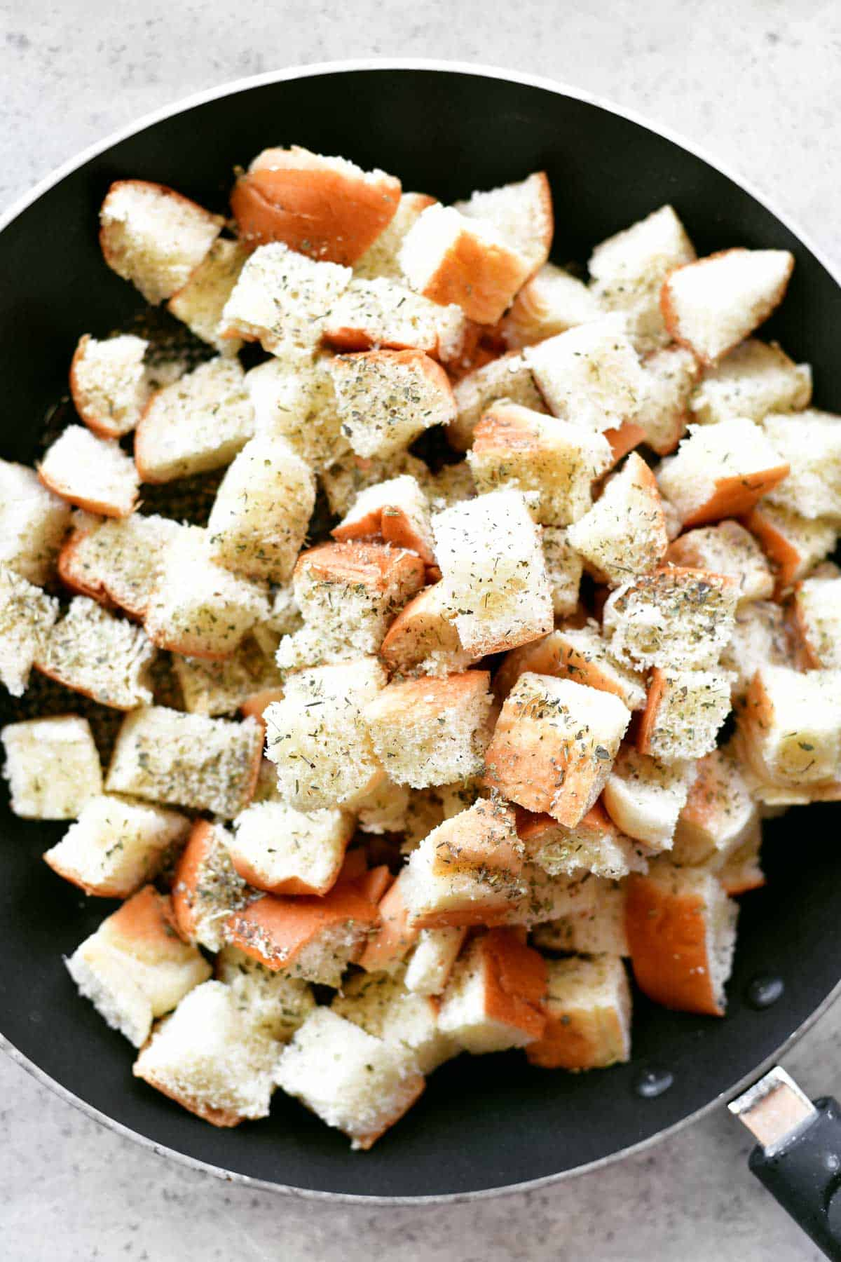 cubed bread with spices in skillet for croutons recipe