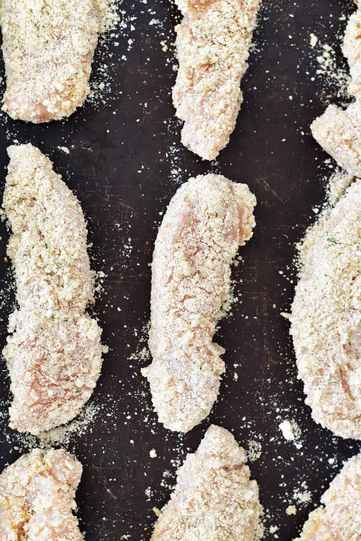 coated garlic parmesan chicken tenders on a baking sheet