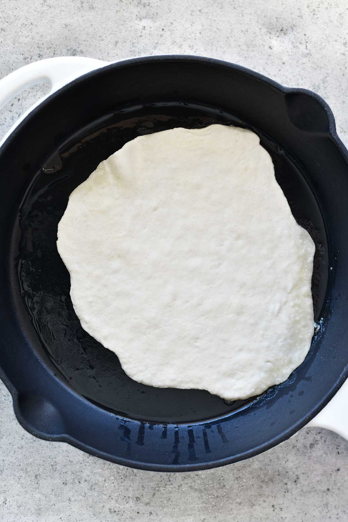 frying two ingredient dough in cast iron skillet for naan flatbread