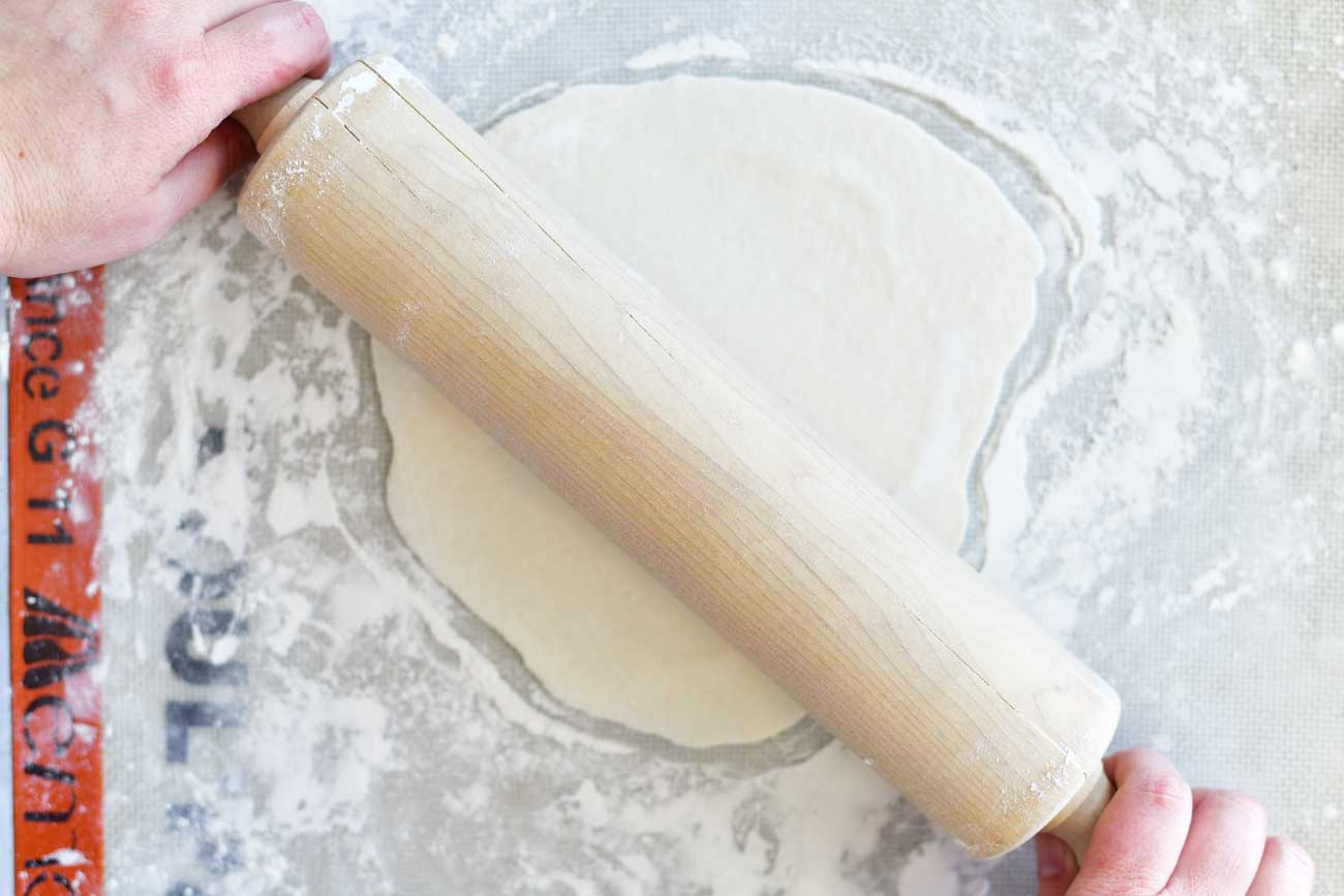 rolling out two ingredient dough for naan flatbread