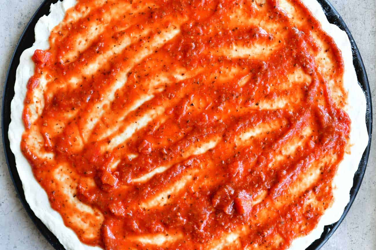 spread sauce on two ingredient pizza crust