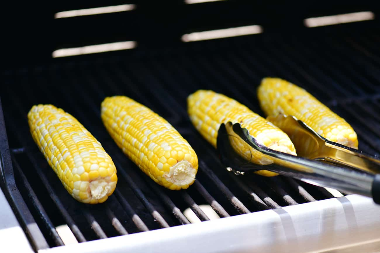 flipping grilled corn on the cob peeled