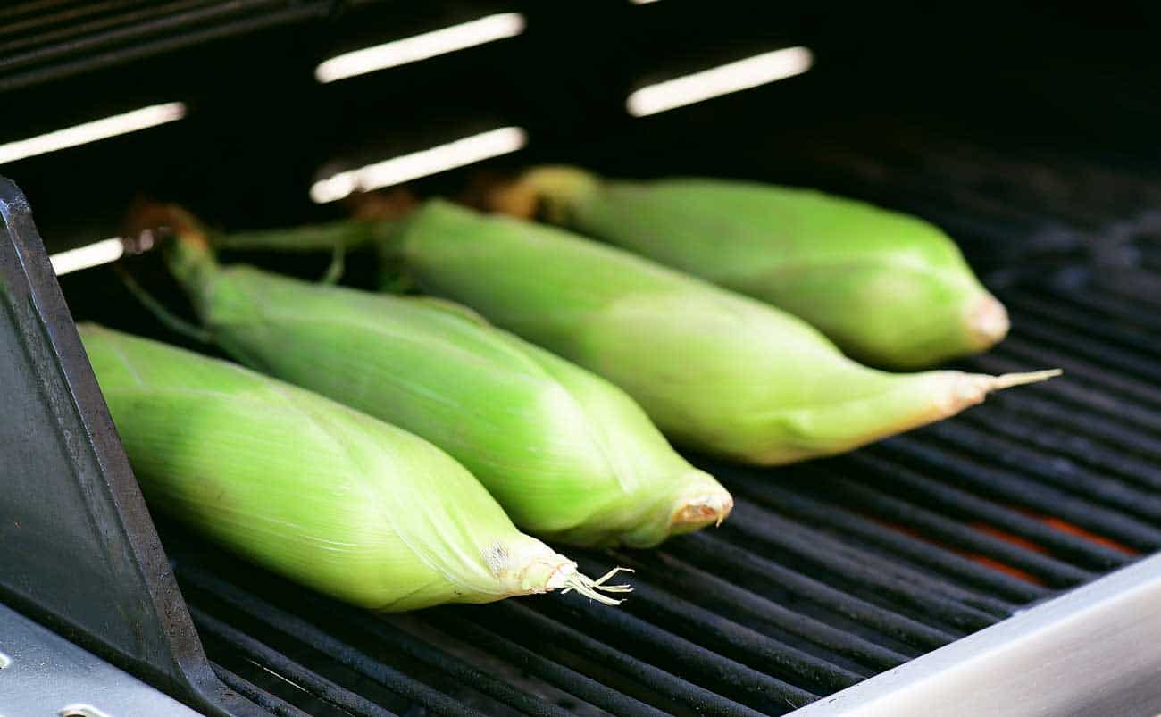 corn on the cob on the grill with the husks