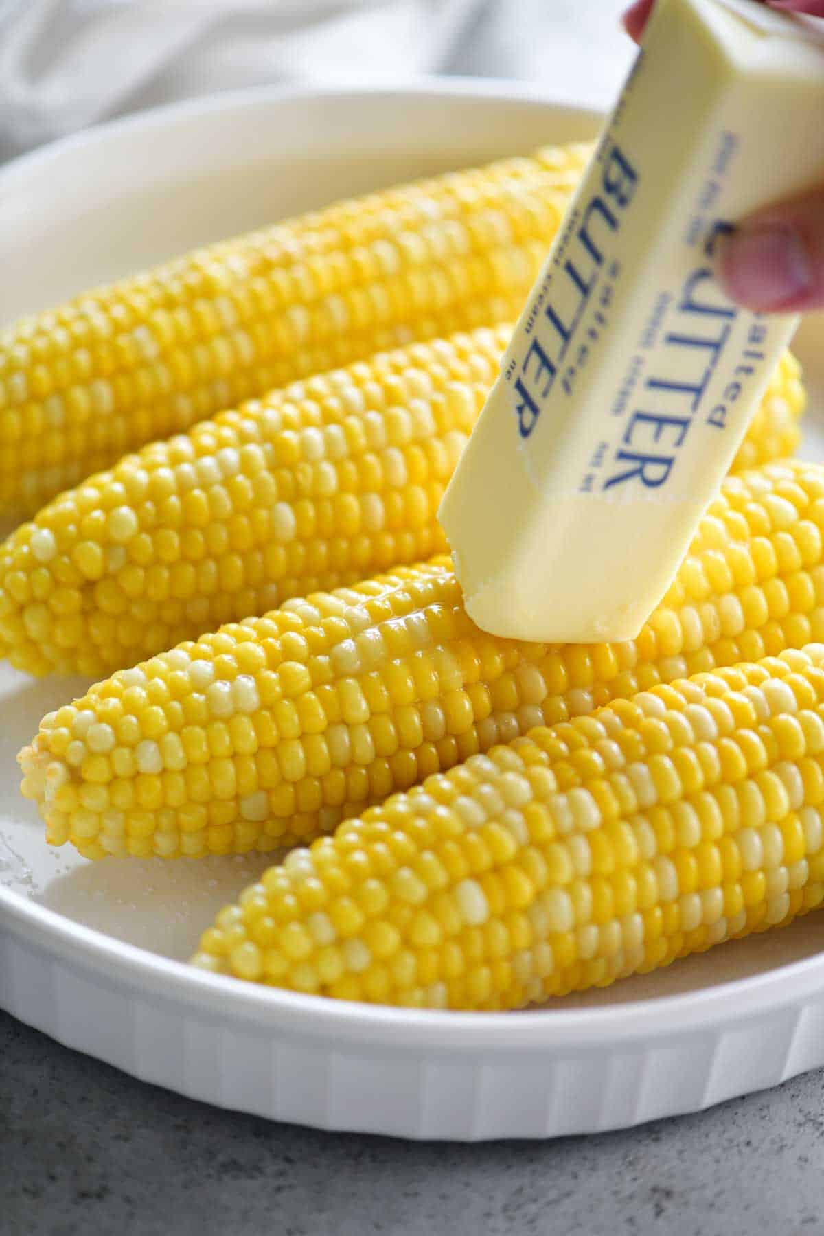 buttering boiled corn on the cob