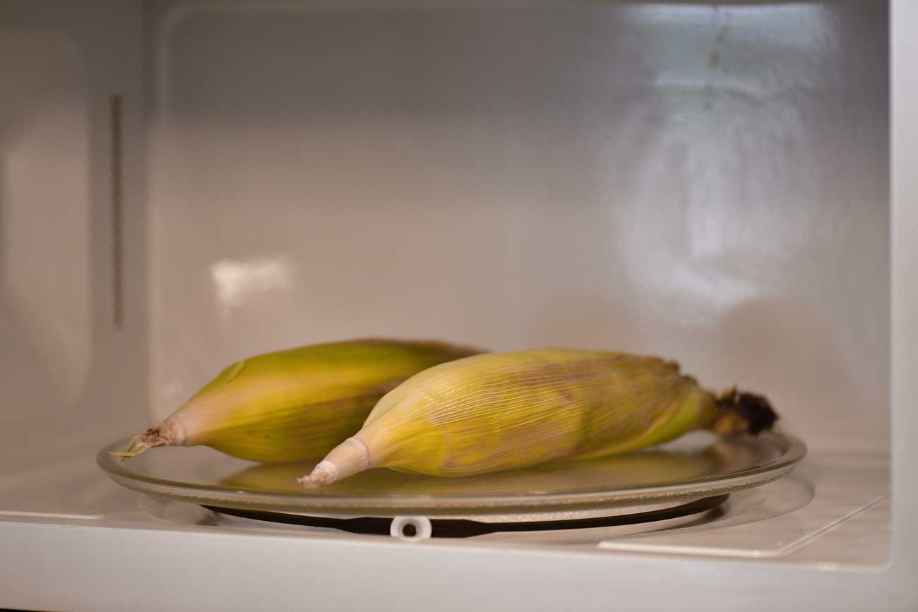 place corn on the cob with the husks in the microwave