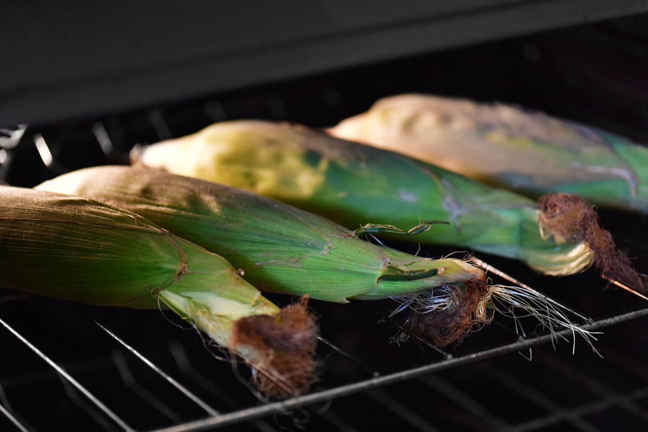 Oven roasted corn on the cob with the husks on the oven racks