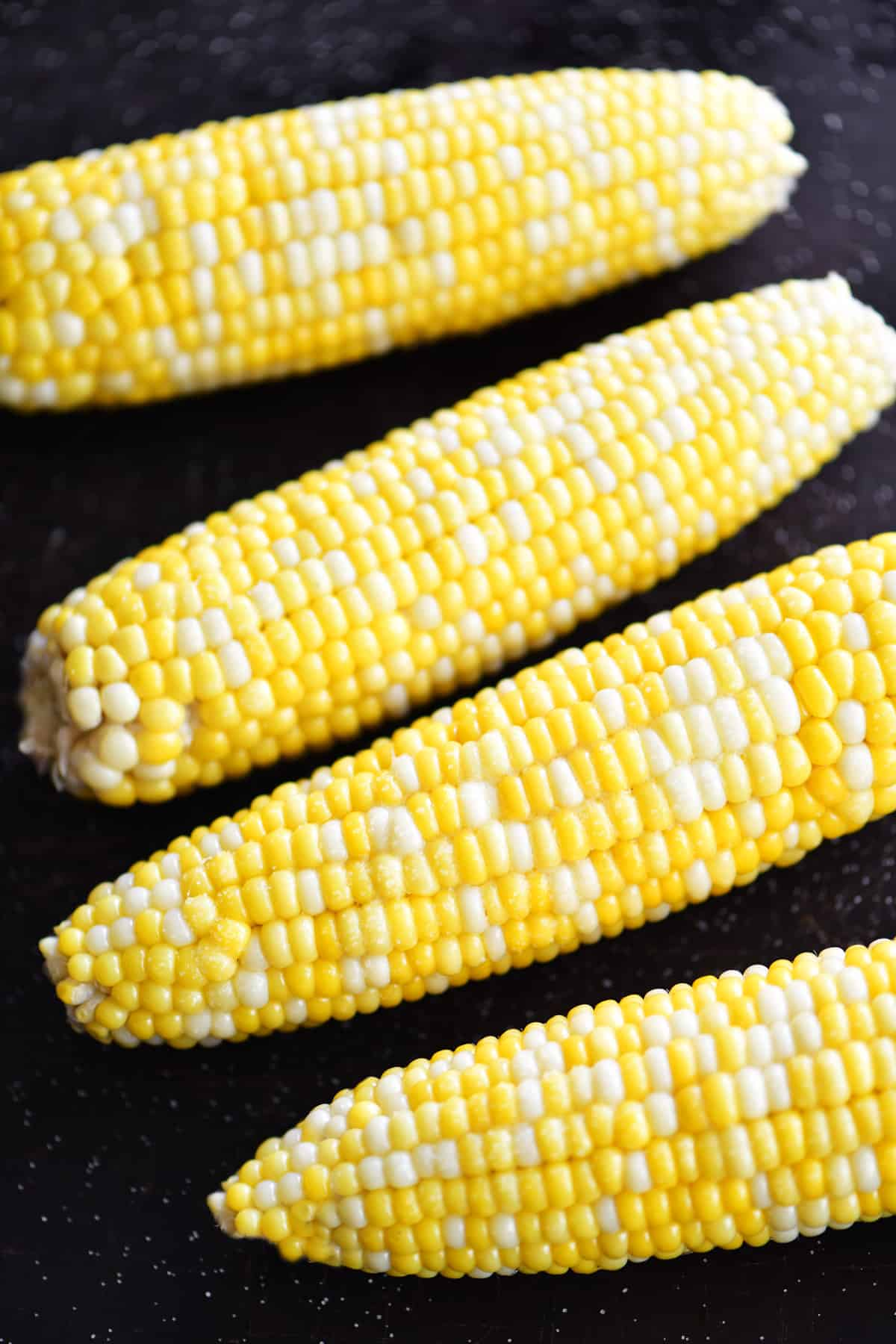 oven roasted corn on the cob with husks buttered