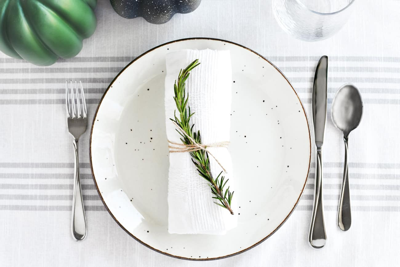 Thanksgiving table setting with plate, silverware, napkin and rosemary sprig