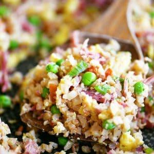 scoop of pork fried cauliflower rice in wooden spoon