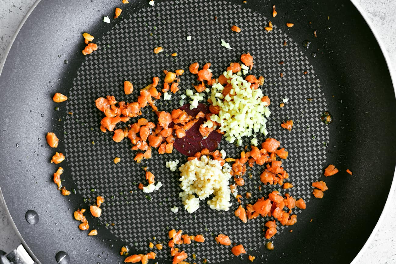 minced ginger, garlic and carrots in frying pan for pork fried cauliflower rice