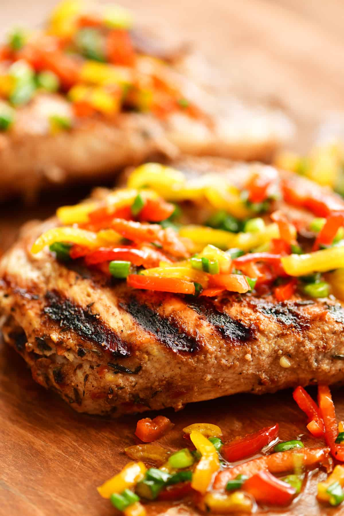 grilled Jamaican jerk chicken breast with sliced peppers and onions on top