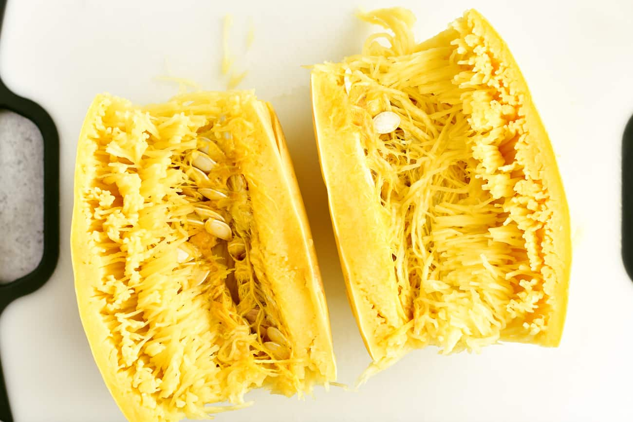 cooked spaghetti squash sliced in half with seeds and pulp inside