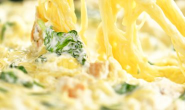scooping spinach artichoke spaghetti squash with chicken from skillet