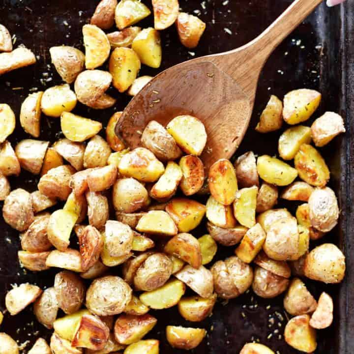 oven roasted potatoes in sheet pan with wooden spoon