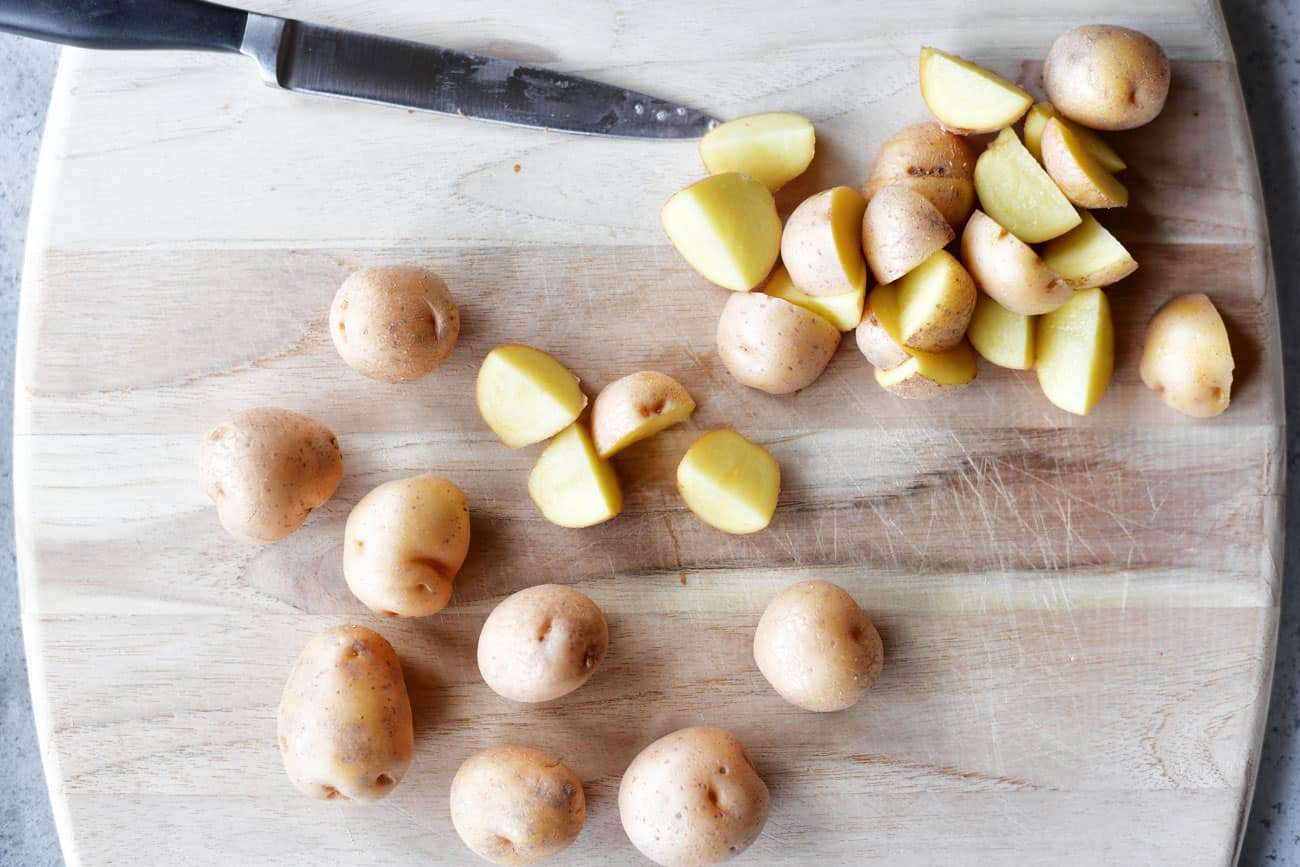small potatoes being sliced on cutting board