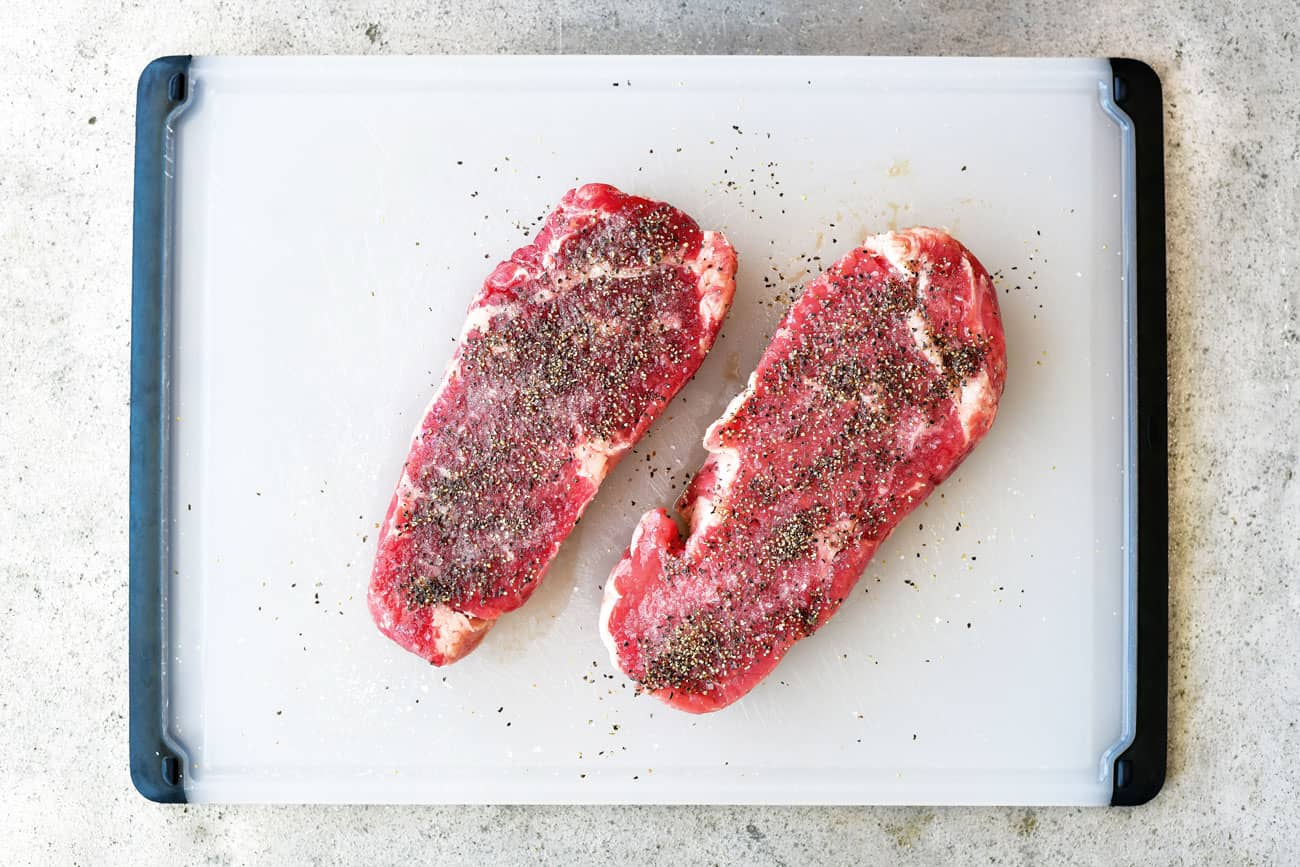steak on a white cutting board seasoned with olive oil salt and pepper