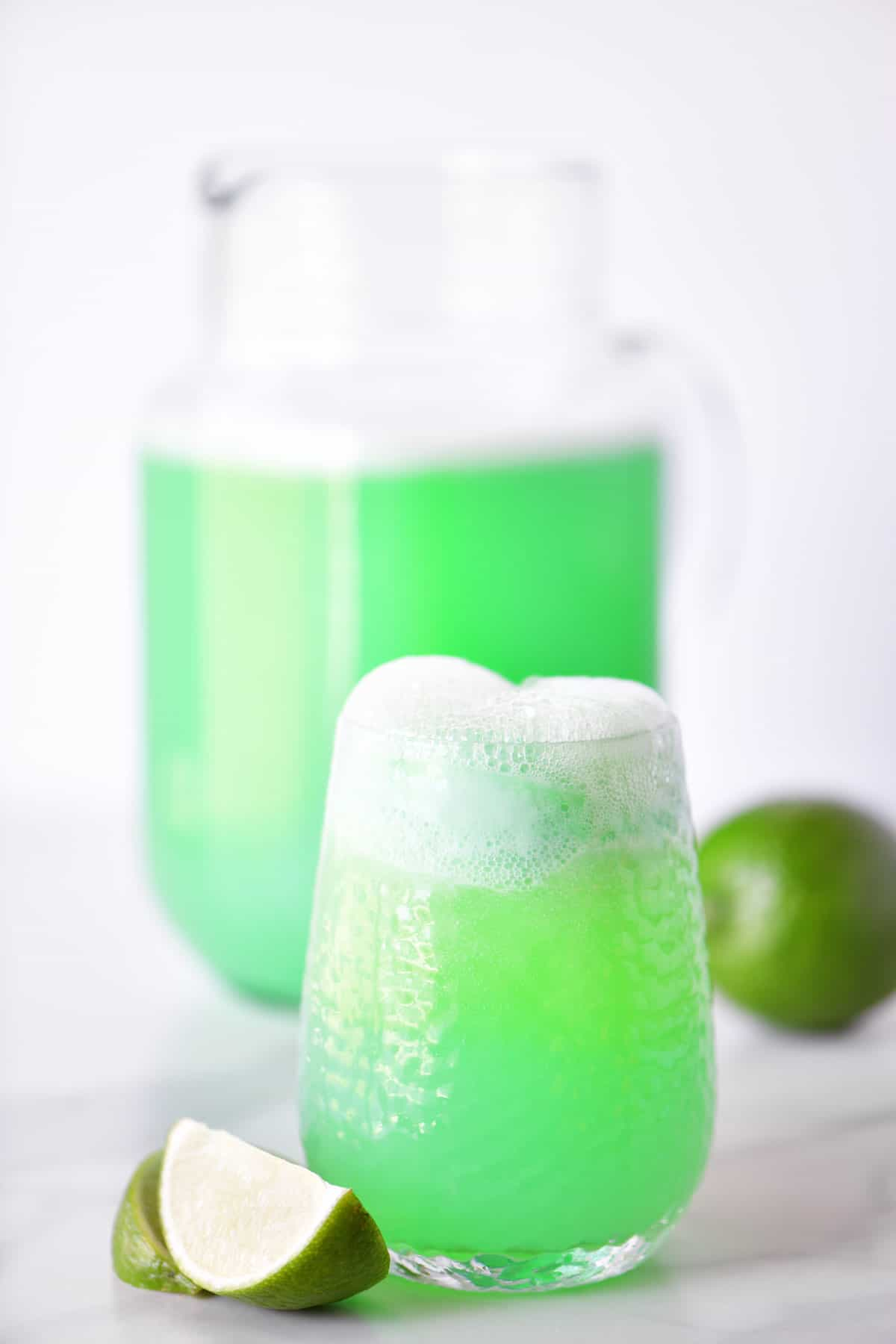 lime sherbet punch in a glass and a pitcher with lime wedges
