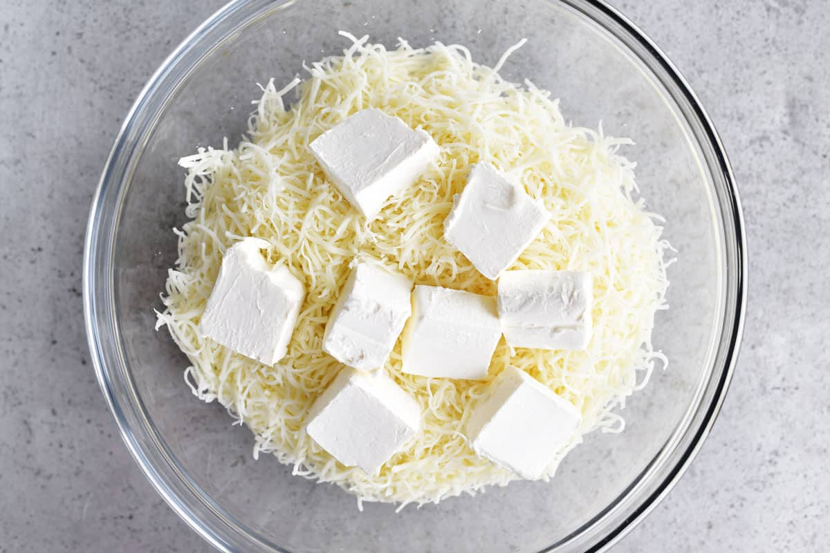 shredded mozzarella cheese and cubed cream cheese in a glass bowl