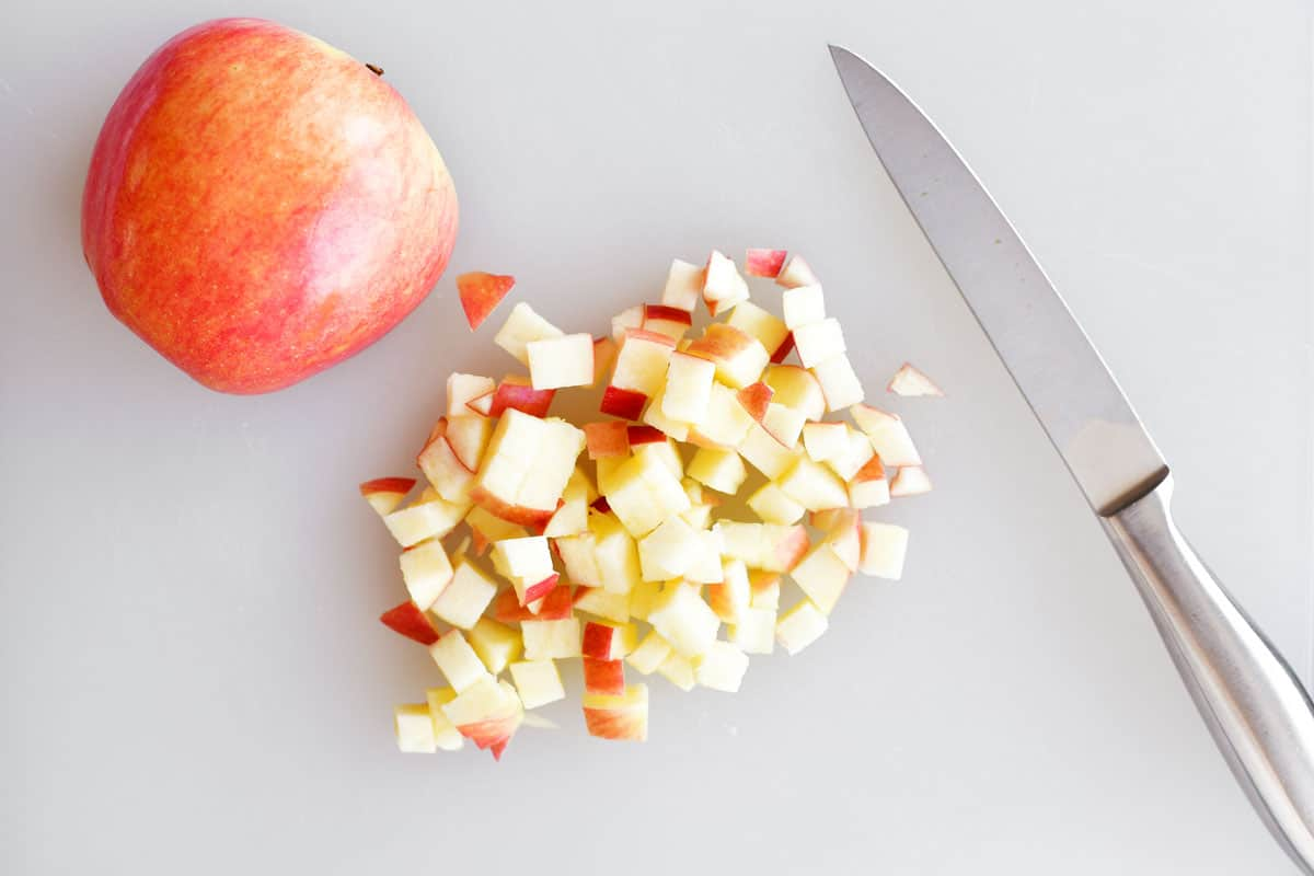 diced apples on a cutting board with a knife