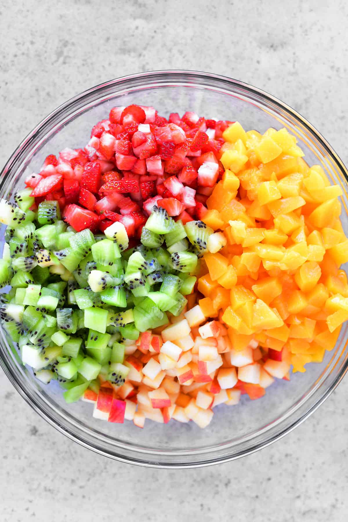 diced apples, peaches, strawberries, and kiwi in a glass bowl